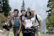 Cinq amis randonneurs posent devant une montagne