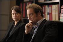 Un homme et une femme assis dans un bureau, derrière eux, des dossiers