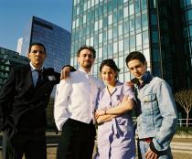 Les quatre personnages principaux du film devant le gratte-ciel de la multinationale qu'ils combattent