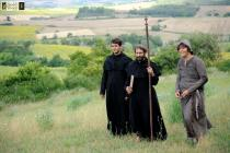 Deux moines et un homme en costume médiéval marchent dans une plaine verdoyante
