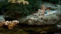 Une femme et une petite fille blonde sont allongées sur un rocher qui surplombe une rivière