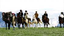 Groupe de cavaliers sur une plaine au milieu des montagnes