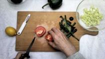 Une main coupe des légumes sur une planche à découper en bois