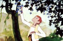 Un jeune singe cueille des fleurs bleues dans un arbre