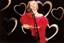 Une jeune femme portant une robe et un boa rouges, chante dans un micro, dans un décor noir avec des coeurs dorés