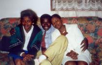 Photo de famille d'un homme et de ses deux femmes, assis sur un canapé