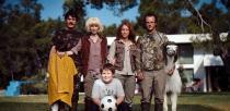 Photo posée d'un groupe d'amis, de leurs enfants et d'un lama, dans un jardin, devant une maison blanche
