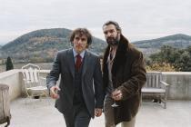 Jean Dujardin et Albert Dupontel marchant sur une terrasse avec un air décidé