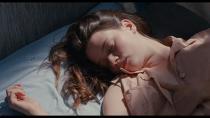 Jeune fille assoupie sur un lit aux draps blancs