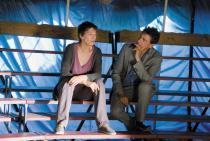 Couple assis sur les gradins d'un cirque au chapiteau bleu ciel