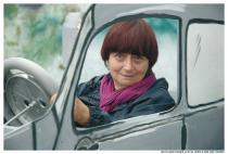 Agnès Varda au volant d'une voiture grise en carton-pâte
