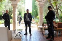 Dans une villa aux colonnes romaines, un homme et deux autres, armés vêtus de noir