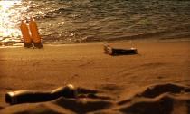 Coucher de soleil sur la plage où sont éparpillées deux bouteilles jaunes et deux bottes noires