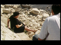 Une femme est assise sur des pierres, un homme la regarde d'en-haut