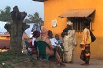 Une groupe de femmes et d'enfants d'origine africaine parlent devant une maison jaune